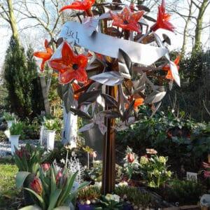 Modern en artistiek RVS en geroest grafmonument met prachtige gekleurde glazen bloemen voor partner