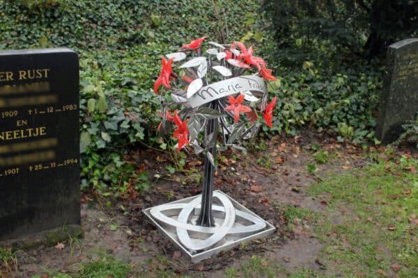 Modern en artistiek grafmonument met prachtige gekleurde glazen bloemen voor partner