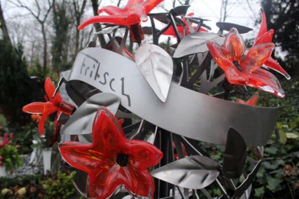 Eigentijds grafmonument met prachtige rode glazen bloemen voor partner