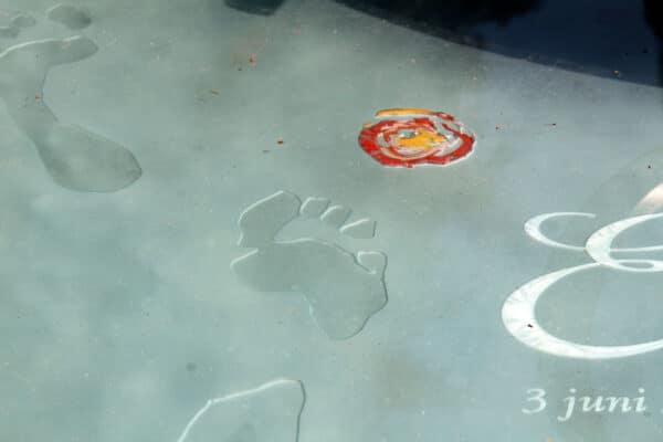 glazen grafsteen met voetafdruk en bloem in glazen grafmonument
