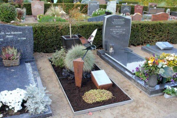 Modern gedenkteken met RVS vogel valk op geroeste zuil vor echtgenoot/partner