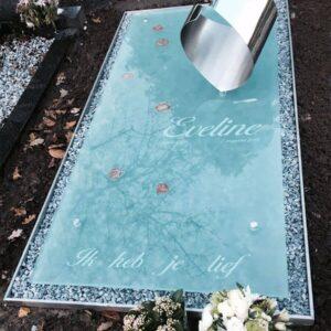 Moderne Grafzerk van glas en RVS met voetafdrukken en bloemen