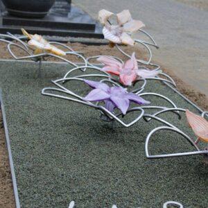 Modern RVS grafmonument met glazen bloemen voor jonge vrouw